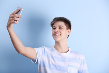 Teenage boy making selfie with mobile phone on light background