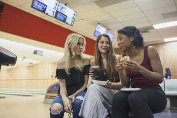 Three young women eatnig at a bowling alley.