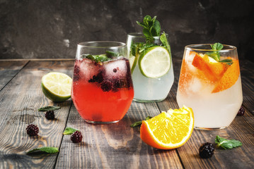 Selection of three kinds of gin tonic: with blackberries, with orange, with lime and mint leaves. In glasses on a rustic wooden background. Copy space