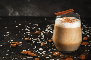 Traditional Mexican drink Horchata Latte - coffee mixed with Horchata, a cocktail of almonds, rice  vanilla and cinnamon. On a black concrete table, with ingredients. Copy space