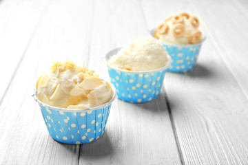 Tasty ice-cream in cups on wooden background