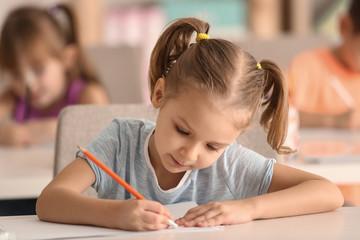 Cute girl drawing in classroom