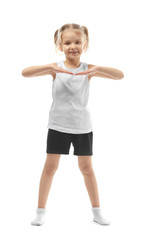Cute girl doing gymnastic exercises on white background