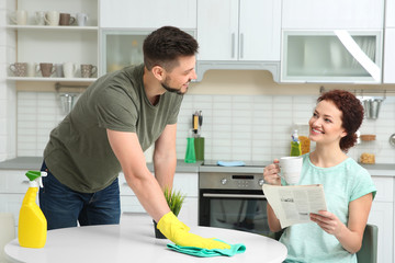 Woman reading newspaper and drinking coffee while man cleaning kitchen