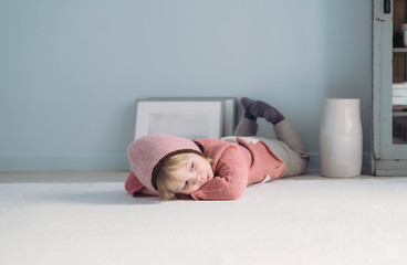 Müdes kleines Mädchen liegt auf dem Boden und ruht sich aus