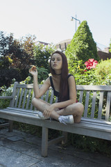 A young woman sitting on a park bench eating an apple