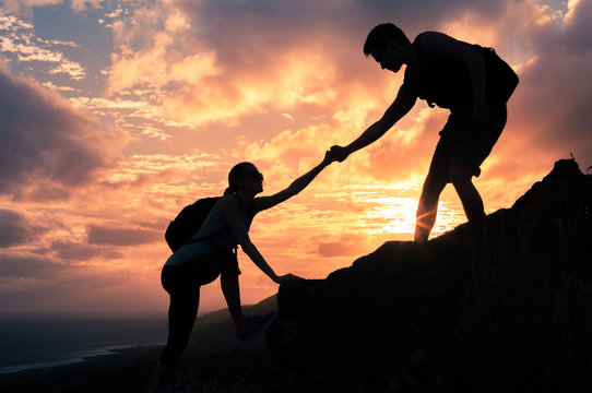 Team work. Man and woman helping each other climb up a mountain.  Giving a helping hand concept.