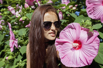 A young woman next to a large flower