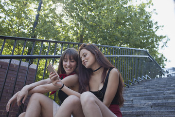 Two young women sitting on a staircase with a smart phone