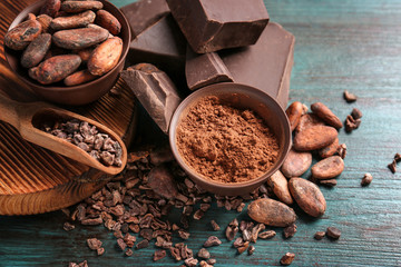 Wall Mural - Bowls of cocoa beans and powder with broken chocolate pieces on color background