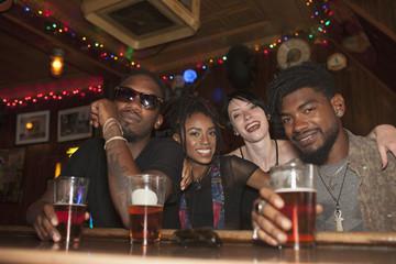 Portrait of smiling friends enjoying at bar