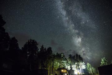 Night starry sky scene with illuminated cottage