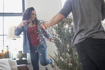 A young woman and man decorating a Christmas tree