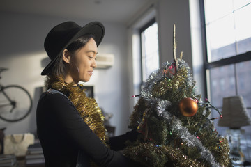 A young woman decorating a Christmas tree