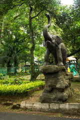 elephant statue standing on rock in front of children playground photo taken in Ragunan zoo Jakarta Indonesia