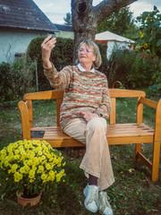 Senior woman is taking a selfie in her garden
