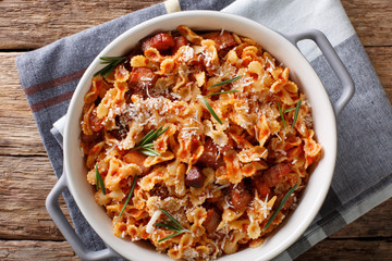 farfaline pasta with tomato, bacon and Parmesan close-up in a saucepan. horizontal top view