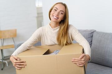 frau sitzt zuhause auf dem sofa und öffnet ein großes paket