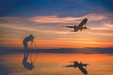Silhouette photographer take photo and silhouette plane fly on sky at sunset in Thailand