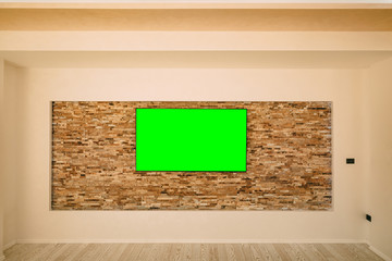 A modern LCD TV with a green screen hanging on the wall.