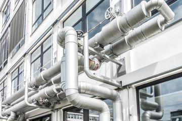 Rohre einer Lüftungsanlage mit Ventilen an einer Gebäudefassade