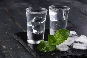 Vodka in shot glasses and ice on rustic wood background