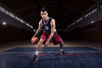basketball player dribbling ball thought the legs