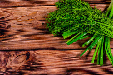Green dill and onion on wooden table. Top view