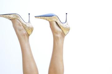 Frauenbeine mit goldenen Stöckelschuhen ragen in die Luft