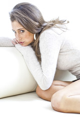 Junge Frau sitzt nachdenklich auf einer Couch