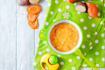 Food for kids, children's lure, organic puree from boiled potatoes and carrot in a bowl on a white rustic wooden background