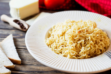 Hearty and delicious dinner, pasta, instant noodles with spices, tomatoes and mozzarella cheese on a dark wooden background