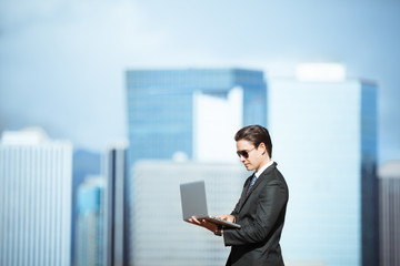 Businessman using laptop computer against cit background. People connecting with technology in the city concept.
