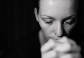 Portrait of woman praying and feeling desperate.