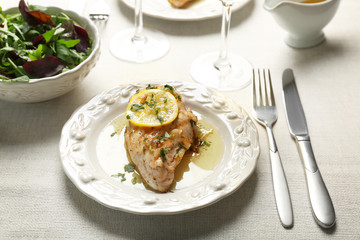 Plate with delicious chicken breast on table