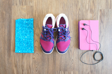pink sneakers, phone in a pink case with headphones and headband on wooden background. Items for Jogging. top view