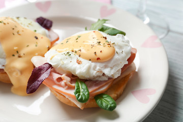 Tasty eggs Benedict on plate, closeup