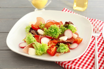 Plate with fresh salad on table, closeup