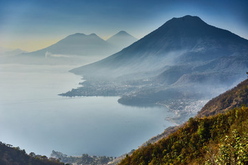 Highlands with volcanoes at Lake Atitlan in Guatemala / Foggy morning at lake in Guatemala in the morning hours