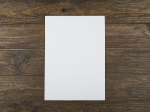 Blank sheet on brown wooden table. Horizontal shoot.