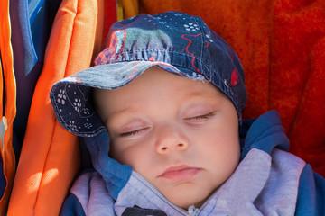 Cute baby boy sleeping in a stroller