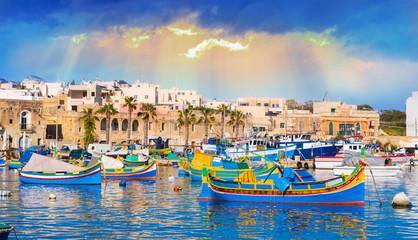 Marsaxlokk village harbor of Malta, illuminate by sunset light