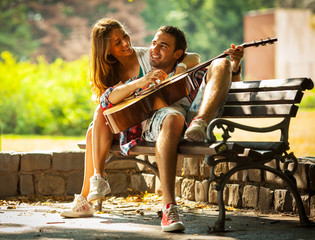 Young man sing and playing guitar to his girlfriend .Relaxing in the nature at the park.