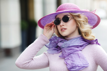 A beautiful stylish blonde woman in a wide-brimmed lilac hat and sunglasses.