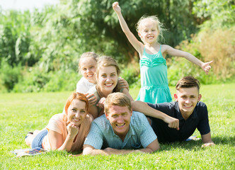Portrait of big modern family with parents and four children lying on green lawn outdoors