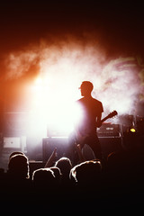 silhouette of guitar player in action on concert stage