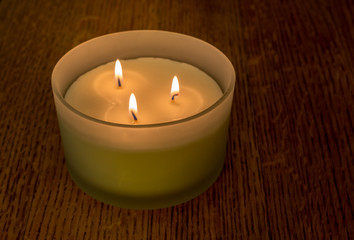 Three flame scented candle in matte glass holder on oak wood table close up