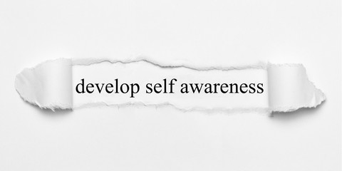 develop self awareness on white torn paper