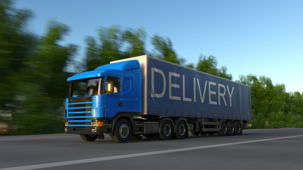Speeding freight semi truck with DELIVERY caption on the trailer. Road cargo transportation. 3D rendering