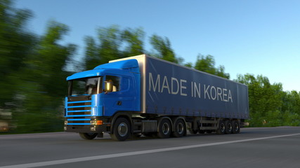 Speeding freight semi truck with MADE IN KOREA caption on the trailer. Road cargo transportation. 3D rendering